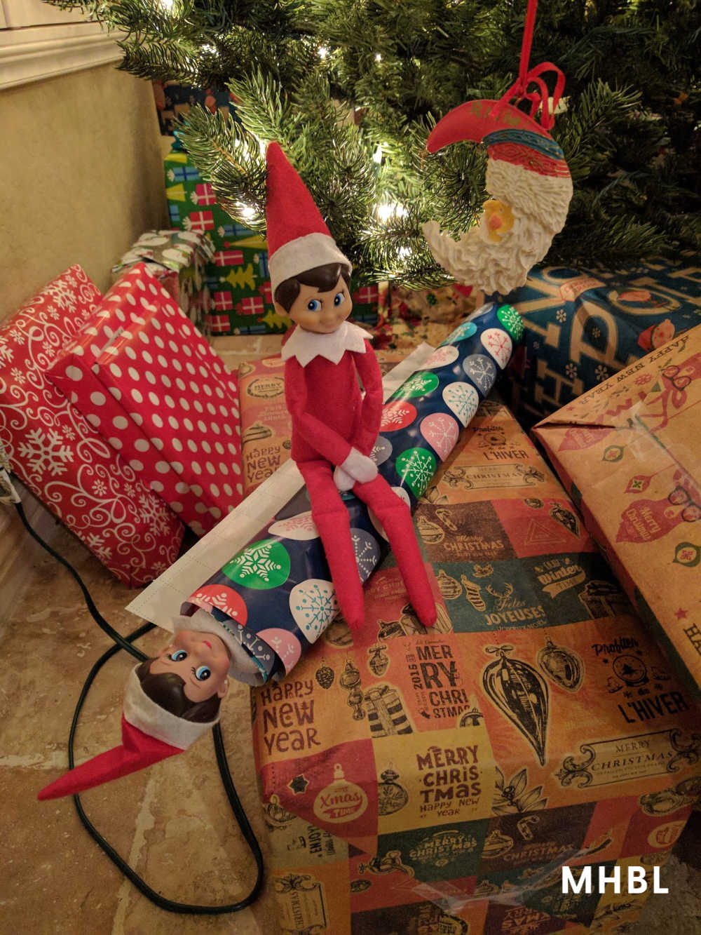 elf on the shelf ideas - elf playing with wrapping paper